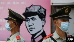 中國武警5月22日在北京人民大會堂南部的一個宣傳畫前站崗。
