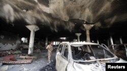 지난 16일 예멘 사나에서 한 군인이 공습으로 파손된 차량을 수색하고 있다.