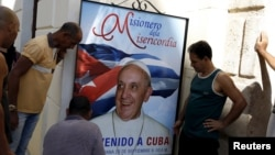 People hang up a poster with a photograph of Pope Francis in Havana, Cuba, Sept. 18, 2015.