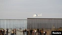 抵达蒂华纳的部分中南美洲移民在边境墙前。