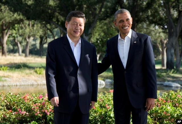 FILE - President Barack Obama stands with Chinese President Xi Jinping at the Annenberg Retreat at Sunnylands as they meet for talks in Rancho Mirage, California, June 7, 2013.