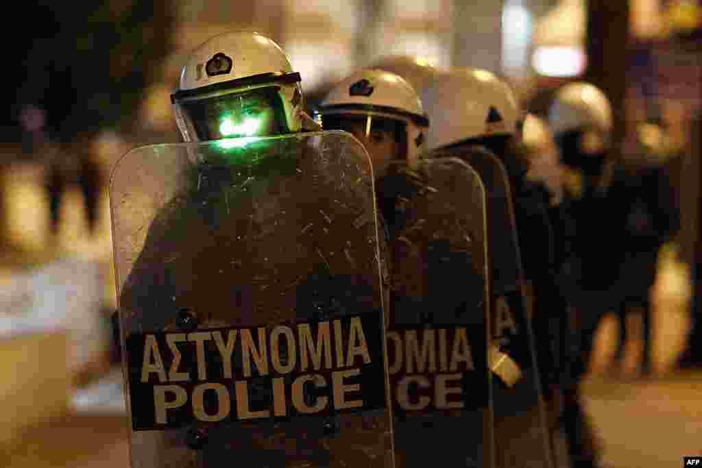 Cảnh sát viên đứng hàng đầu bị người biểu tình tấn công bằng tia laser trong khi xô xát trước trụ sở Quốc hội ở Athens, 19 tháng 2, 2012. (AP)