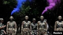 Khói bốc lên từ đầu những người nộm bên cạnh binh sĩ Trung Quốc trong một lần tập bắn đạn thật.
