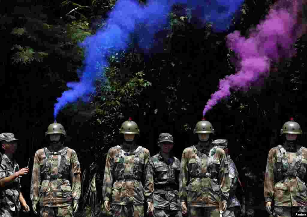 Fumaça sai de capacetes de manequins ao lado de soldados do Exército de Liberação do Povo chinês durante um exercício militar em uma base naval em Hong Kong em comemoração do décimo oitavo aniversário da entrega do território à China pelos britânicos.
