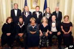 Teresa Heinz Kerry, front row, from left, Kennedy Center Honorees Al Pacino, Mavis Staples, Martha Argerich, James Taylor, and Kennedy Center President Deborah Rutter; rear row, from left, Secretary of State John Kerry, Kennedy Center Honorees Joe Walsh, Don Henley, and Timothy Schmit, and David Rubinstein are photographed following the State Department for the Kennedy Center Honors gala dinner, Dec. 3, 2016, in Washington.