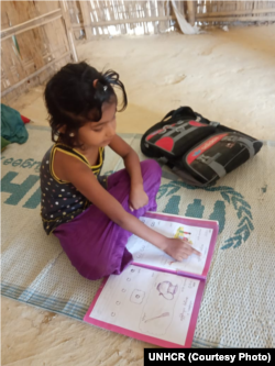 Grade 1 Learner Using Workbook at home in Rohingya Refugee Camp, Cox's Bazar, Bangladesh