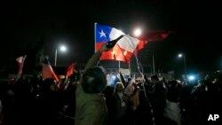 Una multitud se reunió frente al Hospital Militar de Santiago ondeando banderas chilneas celebrando la muerte del general Manuel Contreras, el sábado, 8 de agosto de 2015.