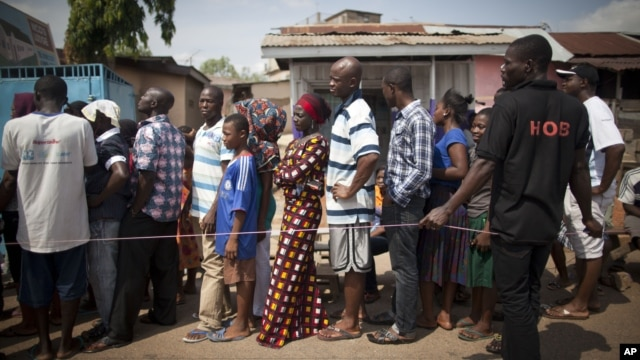 People wait in line to vote during an unexpected second day of balloting at a polling station near Accra, Ghana, Dec. 8, 2012.