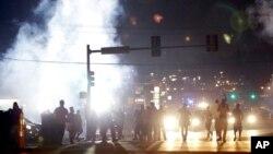 18일 미국 미주리주 퍼거슨 시에서 흑인 청년이 백인 경찰의 총에 맞아 사망한 사건에 항의하는 시위가 계속된 가운데, 시위대 주변으로 경찰이 발사한 최루탄 연기가 피어오르고 있다.