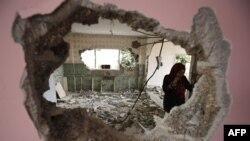 Seorang perempuan memeriksa rumah warga Palestina, pelaku serangan di Tepi Barat, di desa Kobar, dekat Ramallah, yang dirobohkan oleh pihak berwenang Israel. (Foto: dok).