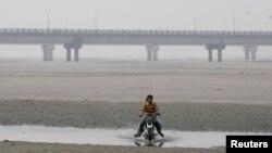 دریائے چناب کے خشک علاقے سے ایک نوجوان اپنی موٹر سائیکل گزار رہا ہے۔ فائل فوٹو