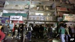 People gather in front of the mall in Baghdad, Iraq, on Jan. 11, 2016. Gunmen stormed into the mall Monday, spraying bullets at shoppers before blowing themselves up.