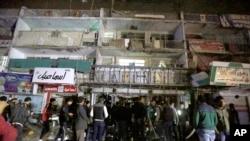 Warga berkumpul di depan sebuah mall di Baghdad, Senin (11/1). Kawanan bersenjata menembaki para pengunjung sebelum meledakkan diri di sebuah pusat perbelanjaan Baghdad, menewaskan sedikitnya 18 orang.