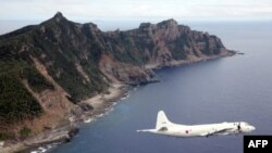 A Japanese Maritime Self-Defense Force plane flies over disputed islets, known as the Senkaku islands in Japan and Diaoyu islands in China, in the East China Sea. (FILE)