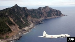 FILE - A Japanese Maritime Self-Defense Force plane flying over the disputed islets known as the Senkaku islands in Japan and Diaoyu islands in China, in the East China Sea.