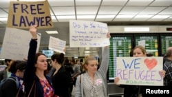 Lawyers offer free counseling as they join dozens of pro-immigration demonstrators cheering and holding signs as international passengers arrive at Dulles International Airport to protest President Donald Trump's travel ban in suburban Washington, Jan. 29