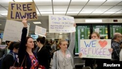 FILE - Lawyers offer free counseling as they join dozens of pro-immigration demonstrators cheering and holding signs as international passengers arrive at Dulles International Airport to protest President Donald Trump's travel ban in suburban Washington, Jan. 29, 2017.