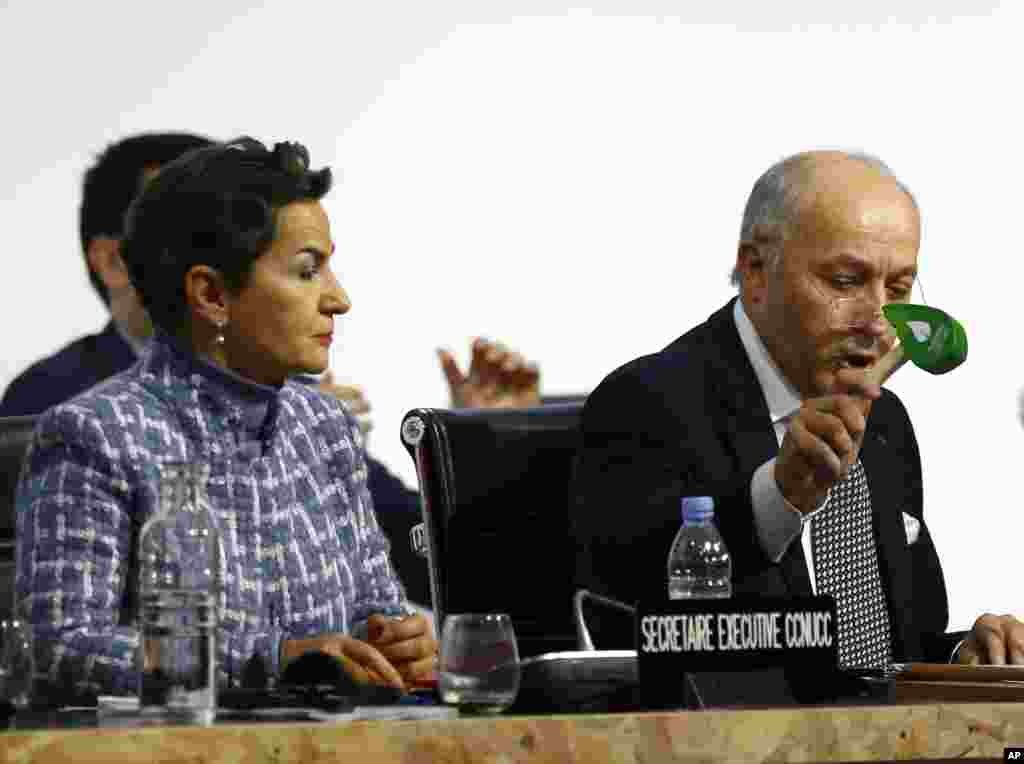 French Foreign Minister and president of the COP21 Laurent Fabius uses to hammer to to mark the adoption of the agreement while United Nations climate chief Christiana Figueres looks on.