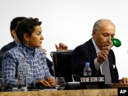 French Foreign Minister and president of the COP21 Laurent Fabius uses to hammer to mark the adoption of the agreement while United Nations climate chief Christiana Figueres looks on.
