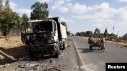 Một chiếc xe ngựa kéo đi qua một chiếc xe tải bị đốt cháy trong cuộc biểu tình ở Oromiya hôm 17/12.
