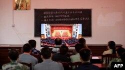广西柳州一个村庄的村民正在观看在北京人大会堂举行的全国脱贫攻坚总结表彰大会的电视直播。(2021年2月25日)