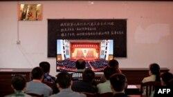 廣西柳州一個村莊的村民正在觀看在北京人大會堂舉行的全國脫貧攻堅總結表彰大會的電視直播。 (2021年2月25日)