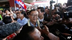 FILE - Sam Rainsy, center, leader of the opposition Cambodia National Rescue Party (CNRP), talks to journalists upon his arrival at Phnom Penh International Airport in Phnom Penh, Cambodia, Aug. 16, 2015. (AP Photo/Heng Sinith)