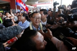 FILE - Sam Rainsy, center, leader of the opposition Cambodia National Rescue Party (CNRP), talks to journalists upon his arrival at Phnom Penh International Airport in Phnom Penh, Cambodia, Aug. 16, 2015.