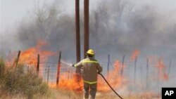 A volunteer firefighter fights a fire which began outside Marfa, Texas, and was carried by winds to nearby Fort Davis, April 9, 2011