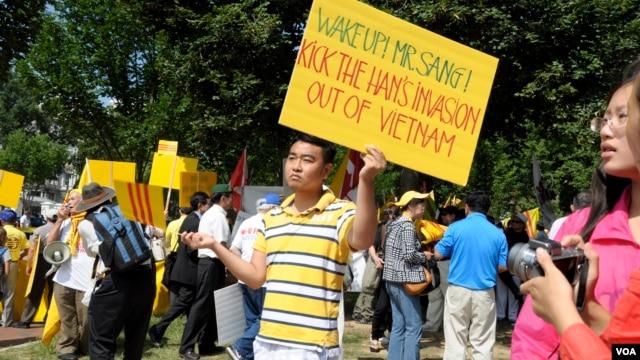 Một thanh niên biểu tình cầm biểu ngữ với hàng chữ kêu gọi Chủ tịch Sang hãy hành động để đánh đuổi Trung Quốc xâm lược ra khỏi Việt Nam.