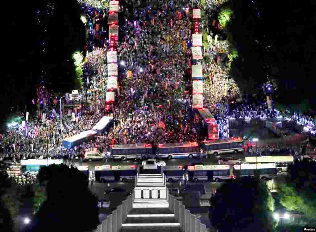 Thousdands of protesters rally against Japan's Prime Minister Shinzo Abe's security bill and his administration, as police use parked buses to block protesters in front of the parliament building (bottom) in Tokyo, in this photo taken by Kyodo.