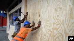 A worker nails a board to use on a storefront window as protection against hurricane Matthew in Kingston, Saturday, Oct. 1, 2016. One of the most powerful Atlantic hurricanes in recent history is also headed toward eastern Cuba and western Haiti.