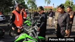 Pejabat Walikota Surabaya Nur Wiyatno memeriksa petugas Satuan Perlindungan Masyarakat (Linmas) yang akan ikut membantu pengamanan Natal dan Tahun Baru di halaman Balai Kota, Selasa, 22 Desember 2015. (VOA/Petrus Riski)