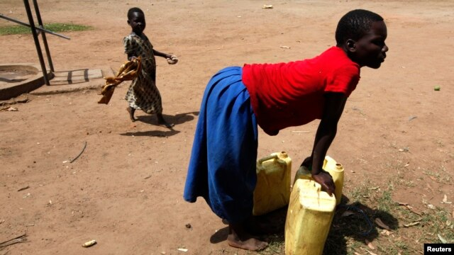 FILE- A girl prepares to lift a jerry can of water onto her head in the village of Loro in the Oyam district of northern Uganda.