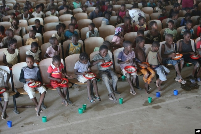 Children sit on benches in a hall after receiving food and drinking water at a temporary shelter for children in Pemba city, on the northeastern coast of Mozambique, May 2, 2019.