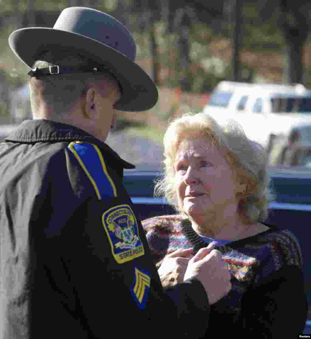 Una mujer conversa con un oficial de la Patrulla Estatal de Connecticut en busca de noticias sobre el tiroteo en la escuela, en Newtown, Connecticut.