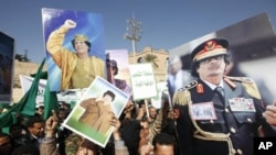 Supporters of Libyan leader Moammar Gadhafi hold his pictures as they take part in a pro-government rally in Tripoli, February 17, 2011