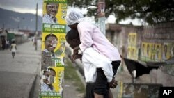 Man, carrying woman with cholera symptoms, walks past campaign posters showing presidential candidate Jude Celestin in Port-au-Prince, Haiti, 11 Nov., 2010.