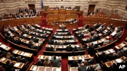 FILE - Greece's lawmakers attend a parliament session before a vote for an omnibus reforms bill in Athens, March 30, 2014.
