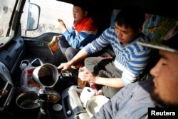 Three men eat a dinner of instant noodles and dried beef inside a truck. Bataa Davaasuren, director of Mongolia's Customs House at Gashuun Sukhait, said customs on both sides of the border were short-staffed.