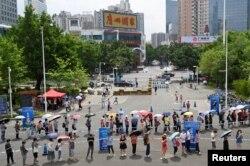 Warga berbaris untuk menerima vaksin COVID-19, di luar tempat vaksinasi di Guangzhou, provinsi Guangdong, China 29 Mei 2021.(cnsphoto via REUTERS)