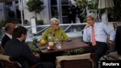 El secretario de Estado de EE.UU., John Kerry, consulta con miembros de la delegación estadounidense en la terraza del hotel donde se realizan las conversaciones nucleates con Irán el jueves, 2 de julio de 2015.
