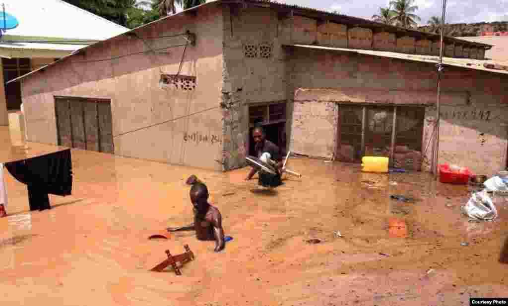 wakazi wawili wajaribu kuokoa mali zao kufuatia mafuriko dar Es Salaam