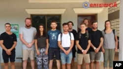 "In this file photo dated Jan. 27, 2018, issued by Cambodian National Police, a group of foreigners stand after they were arrested for ""dancing pornographically"" at a party in Siem Reap town, near the country's famed Angkor Wat temple complex."