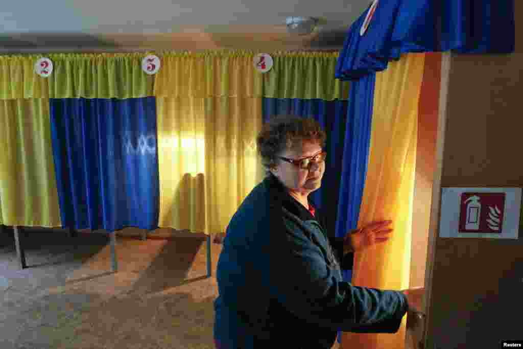 Election commission worker Vera Pozhidaeva demonstrates the readiness of a polling station for Sunday's referendum in the eastern Ukrainian city of Lugansk, May 10, 2014.