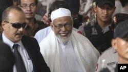 ນັກສອນສາສະໜາຫົວຮຸນແຮງ Abu Bakar Bashir (ກາງ) ພວມອອກຈາກສານມາຫຼັງຈາກພວກຜູ້ພິພາກສາ ໄດ້ຕັດສິນໂທດ ໃນການດຳເນີນຄະດີ ທີ່ສານນະຄອນຫຼວງຈາກາຕ້າ (16 ມິຖຸນາ 2011)