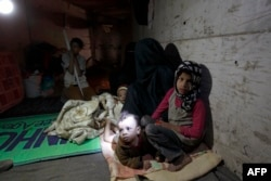 Members of a displaced Yemeni family sit in a manmade underground water tunnel where they are taking shelter after their houses were destroyed by airstrikes carried out by the Saudi-led alliance, in Sanaa, April 30, 2015.