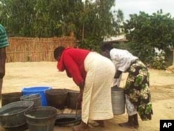 Women collect water from unprotected well