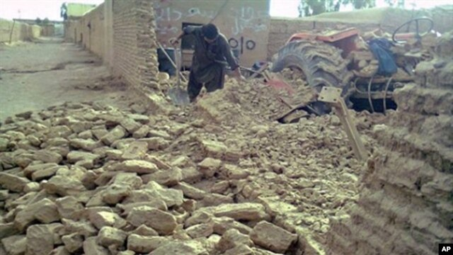 A local resident clears debris of his collapsed mud house following an earthquake in the town of Dalbandin on  19 Jan. 2011.