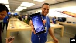 Un representante de Apple muestra un iPhone 6 en una tienda de Canadá.